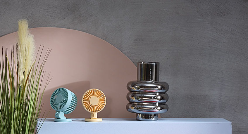 Two mini fans and metal vase beside an artificial plant