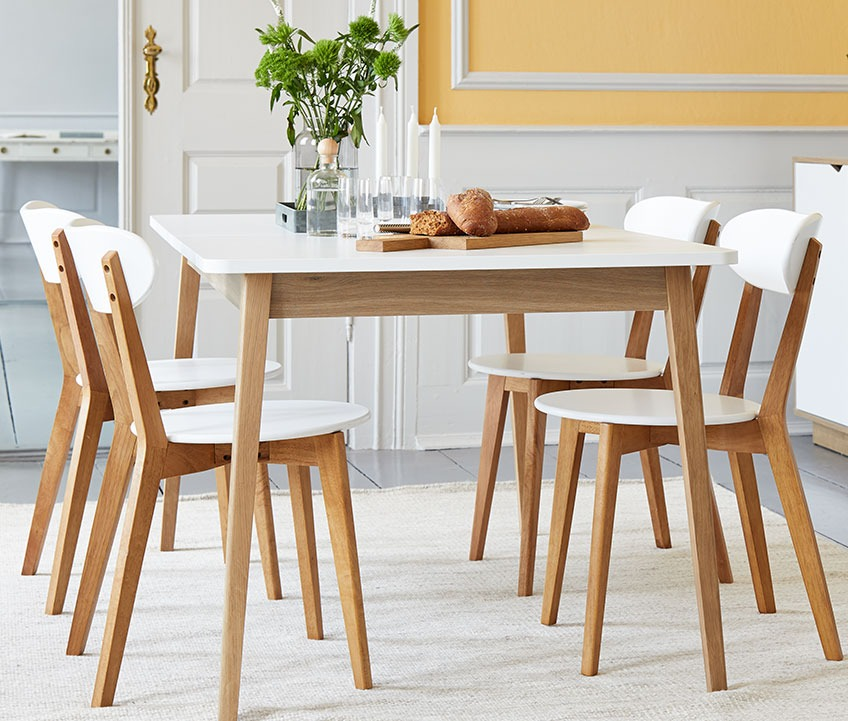 4 dining chairs in wood at a wooden dining table