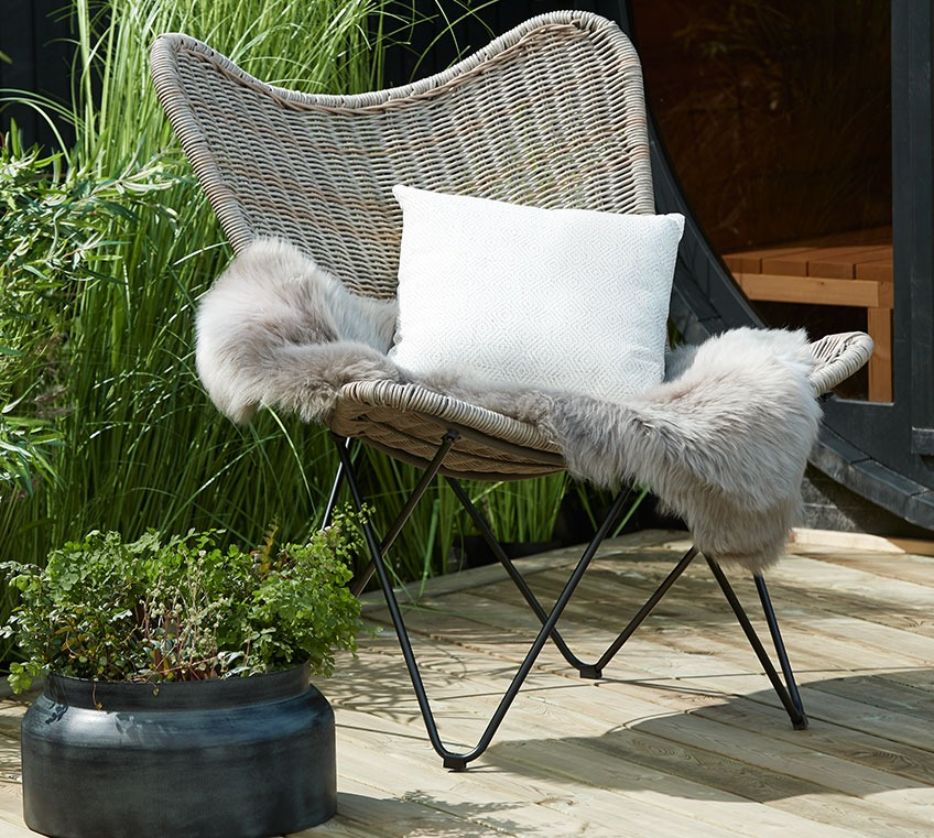 Rattan lounge chair with a hide and a cushion