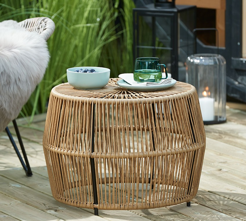 Rattan side table with a bowl and a glass mug